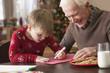 Caucasian grandfather watching grandson write letter to Santa