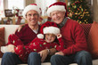 Caucasian father, son and grandson wearing Santa hats