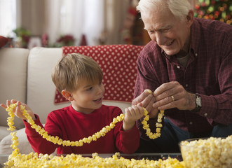 Caucasian grandfather and grandson stringing popcorn