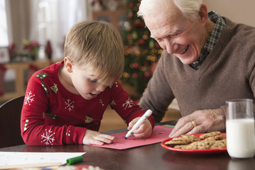 Caucasian grandfather watching grandson write letter to Santa