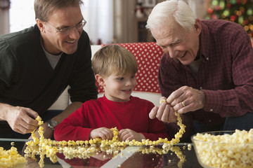 Caucasian father, son and grandson stringing popcorn