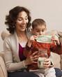 Caucasian grandmother watching grandson putting money in jar
