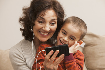 Caucasian grandmother and grandson listening to mp3 player