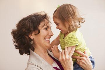 Caucasian grandmother holding granddaughter