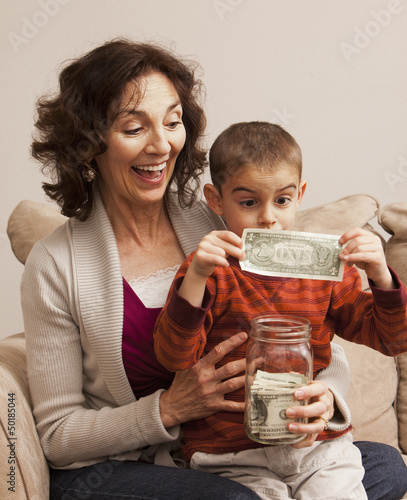 Caucasian grandmother watching grandson putting money in jar