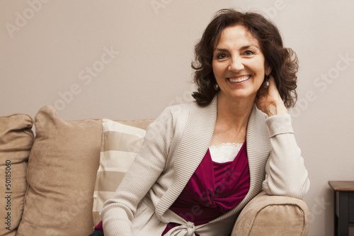 Smiling Caucasian woman sitting on sofa