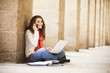Caucasian woman sitting on ground with laptop and talking on cell phone