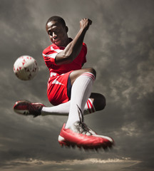 Black soccer player kicking ball