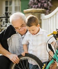 Caucasian grandfather and grandson repairing bicycle