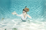 Caucasian businesswoman reaching for money underwater