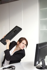 Frustrated businesswoman about to hit computer with keyboard