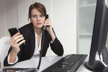 Businesswoman holding cell phone and talking on landline phone