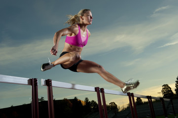 Caucasian runner jumping over hurdles