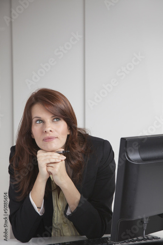 Businesswoman sitting at desk daydreaming