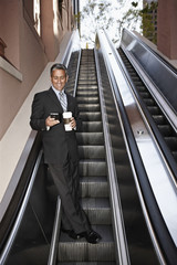 Hispanic businessman text messaging on escalator
