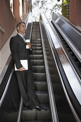 Hispanic businessman on escalator