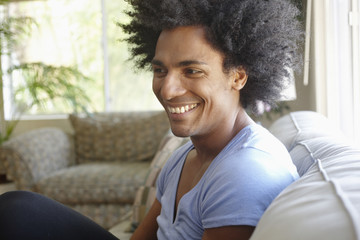 Smiling man sitting on sofa in living room
