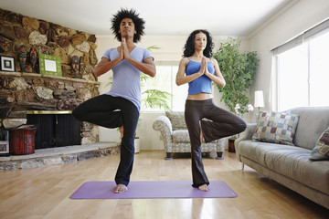 Couple practicing yoga in living room
