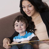 Mixed race mother reading book to son