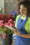 Mixed race florist using digital tablet