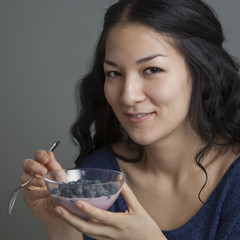 Mixed race woman eating yogurt and fruit