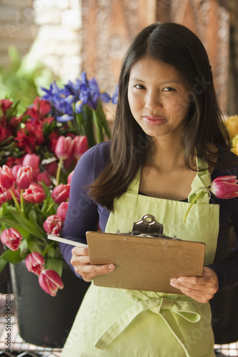 Asian florist holding clipboard