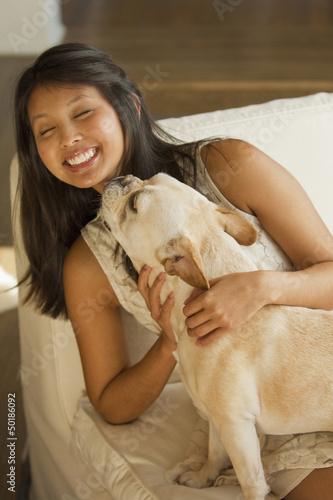 Dog licking Asian woman