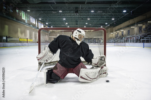 Caucasian hockey goalie blocking puck