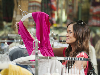 Caucasian woman looking at dress in store