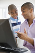 Mixed race man and son using computer together