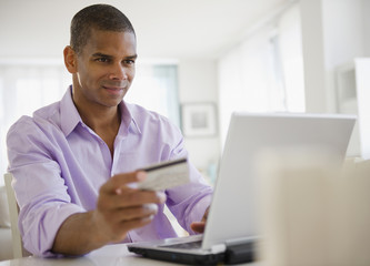 Mixed race man shopping online with credit card