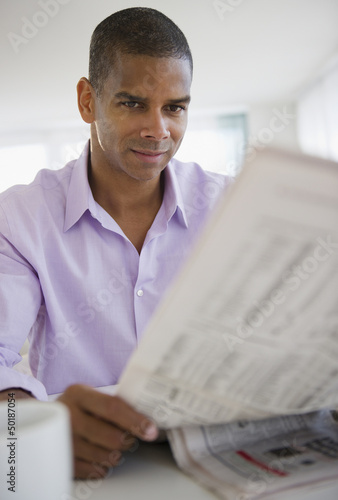 Mixed race man reading newspaper