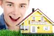 Junger Mann lacht vor Freude mit gelben Haus