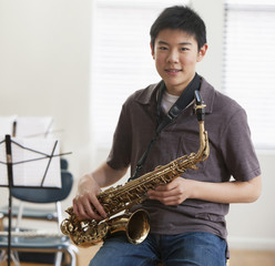 Asian boy holding saxophone