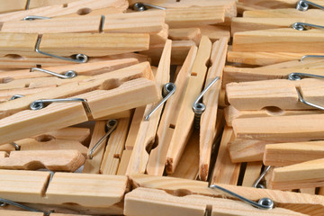 Pile of wooden clothespins as background.