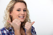 blond woman doing thumbs-up gesture