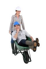 Woman pushing a man in a wheelbarrow