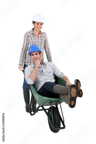 Woman pushing a man in a wheelbarrow
