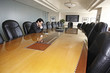 Hispanic businessman sitting in empty conference room
