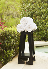Towels on stand near swimming pool