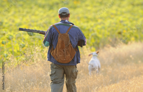 Hunter with dog in a wheat field