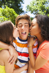Teenage girls kissing male friend