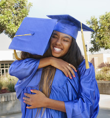 Teenage graduates hugging