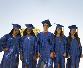 Smiling graduates standing together
