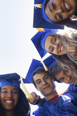 Smiling graduates bending to look at camera