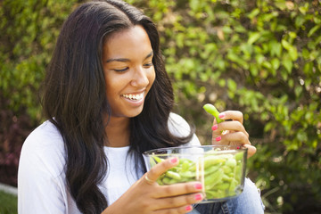 Mixed race teenager eating edamame