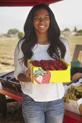 Teenage mixed race girl holding strawberries at fruit stand
