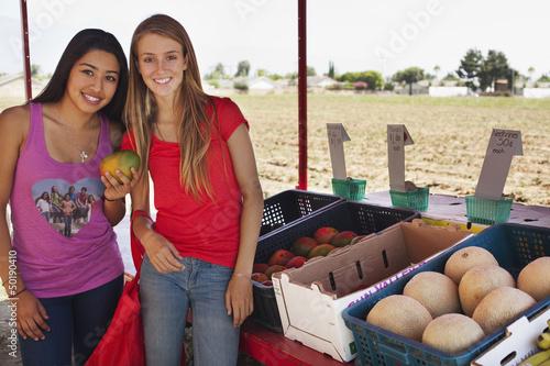Teenage girls shopping at fruit stand