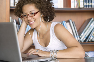 Hispanic woman using laptop in library