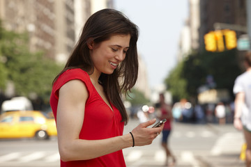 Caucasian woman using cell phone in city street
